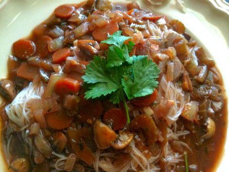 Vegan bourguignon over a plate of rice noodles