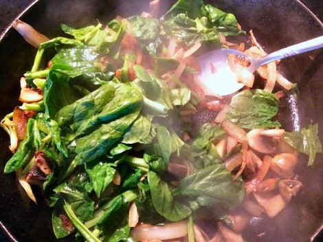 Adding in the spinach to cook